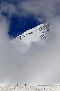 Skiers under Mount Elbrus, Europes highest mountain (5,642m) surronded by clouds, Caucasus, Russia, June 2008  -  Wild Wonders of Europe / Schandy