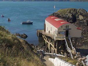 St Davids Lifeboat Station at St Justinian's, with tour boat and fishing-boats in bay. Pembrokeshire, Wales, UK, September 2009. - Norma Brazendale
