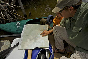 Tim Laman and Russell study their map while on the Hell's Bay Canoe Trail, Everglades National Park. Florida, USA. Model released, April 2008  -  Tim Laman