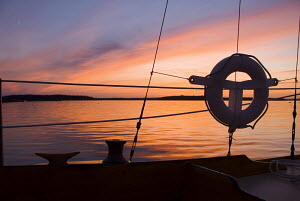 """Detail of Concordia yawl """"Starlight"""" at sunset on Jericho Bay, Maine. July 2007. Property Released. - Benjamin Mendlowitz"""