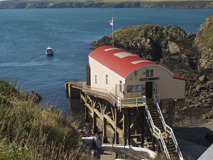 St Davids Lifeboat Station at St Justinian's, with tour boat in bay. Pembrokeshire, Wales, UK. September 2009. - Norma Brazendale