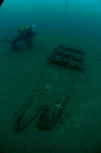 Diver working near the uncovered hull of an unidentified sailing ship off the south coast, UK.. September 2009. - Michael Pitts