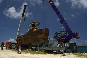 Cranes being rigged to the hulk of tugboat ''Blue Plunder'' prior to towing out to sea and sinking. Nassau, Bahamas. August 2007.  -  Michael Pitts
