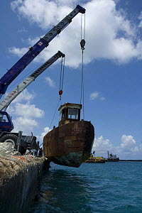 Cranes lowering the hulk of tugboat ''Blue Plunder'' into the water prior to towing out to sea and sinking. Nassau, Bahamas. August 2007.  -  Michael Pitts