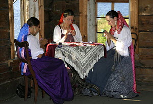 Woman dressed up in traditional costume, sewing embroidery, in wooden museum on Kizhi Island, Lake Onega, Karelia, N Russia, September 2007. - Konstantin Mikhailov
