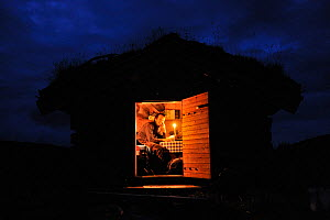 Photographer, Vincent Munier, sitting in small traditional cabin with a grass roof, at night, Forollhogna National Park, Norway, on location for Wild Wonders of Europe, September 2008  -  Wild Wonders of Europe / Munier