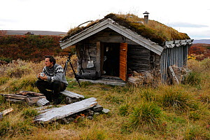 Photographer, Vincent Munier, sitting outside small traditional grass roof hut, Forollhogna National Park, Norway, on location for Wild Wonders of Europe, September 2008  -  Wild Wonders of Europe / Munier