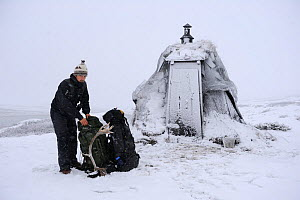 Photographer, Vincent Munier, outside small hut with rucksacks in snow, Forollhogna National Park, Norway, on location for Wild Wonders of Europe, September 2008  -  Wild Wonders of Europe / Munier