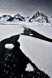 Coastal mountains with sea ice breaking up, Svalbard, Norway, June 2009  -  Andy Rouse