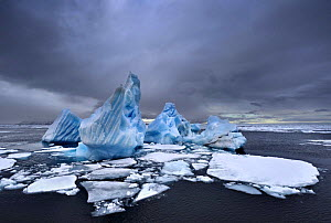 Iceberg and broken pack ice, dark clouds overhead, Svalbard, Norway, August 2007  -  Andy Rouse