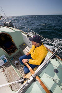 Man helming a Contessa 26 sailing in the English Channel, August 2009. - Richard Langdon