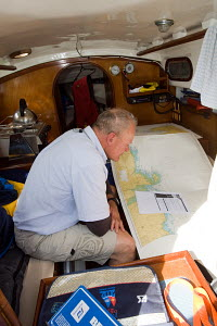 Man navigating with paper charts aboard a Contessa 26 sailing in the English Channel, on the way from Poole, South Coast of England to France, August 2009. - Richard Langdon