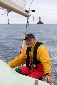 """Man in lifejacket helming a Contessa 26 off the Raz de Sein, with the """"Phare de la Vieille"""" lighthouse in the background. France, August 2009. - Richard Langdon"""