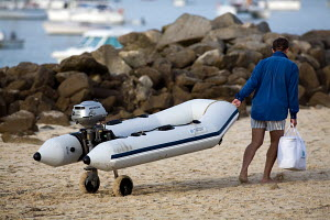 Man dragging his tender (on wheels) up the beach on ile-d'Houat, Brittany, France, August 2009. - Richard Langdon