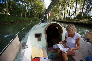 Woman reading naviagation and reference books aboard a Contessa 26 while motoring on the Canal du Midi, France, October 2009. Model released. - Richard Langdon