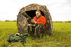 Photographer, Lassi Rautiainen, sitting outside tent, being used as a hide, with camera, Estonia, May 2009  -  Wild Wonders of Europe / Rautiainen