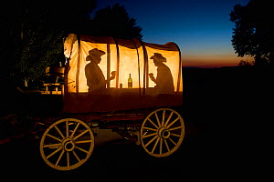 Silhouette of two cowboys playing cards and drinking in a wagon, Wyoming, USA, September 2006, Model released - Jeff Vanuga