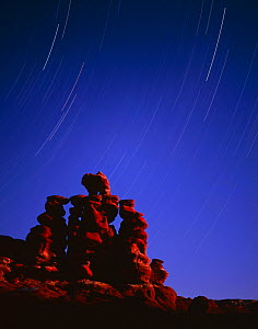 Hoodoo formations of heavily banded sandstone at night with star trails, Navajo Reservation, Arizona, USA  -  Jack Dykinga