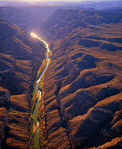 Aerial view of Rio Grande passing through the Boquillas Canyon with the Chisos Mountains and Big Bend National Park in the background, Texas, USA on right of river, Mexico on left of river.  -  Jack Dykinga