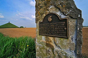 Commemorative stone and plaque near battlefield of the Battle of Waterloo, Eigenbrakel, Belgium, with Lion Hill memorial in the background.  -  Philippe Clement