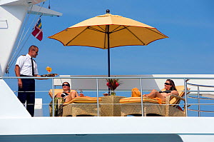 Man serving drinks to two women on a 117' Delta ^Gatster^ cruising in the Exumas, Bahamas. February 2007. Property released and model released.  -  Billy Black