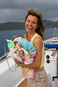 Woman carrying laundry aboard Sunsail Oceanis 523 in the BVI's. March 2006. Model and property released. - Billy Black