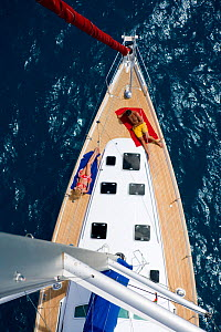 View from the masthead of a couple relaxing on the foredeck of a Sunsail Oceanis 423 in the BVI, March 2006. Model and property released.  -  Billy Black