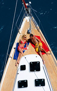 Couple relaxing on the foredeck of a Sunsail Oceanis 423 in the British Virgin Islands, March 2006. Model and property released.  -  Billy Black