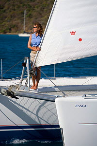 Woman standing on the bow of a Sunsail catamaran cruising in the British Virgin Islands, March 2006. Model and property released.  -  Billy Black