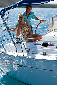 Couple helming a Sunsail yacht sailing in the British Virgin Islands, March 2006. Model and property released.  -  Billy Black