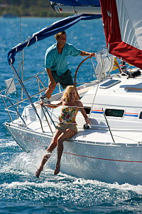 Woman dangling her legs over the side of a Sunsail yacht sailing in the British Virgin Islands, March 2006. Model and property released.  -  Billy Black