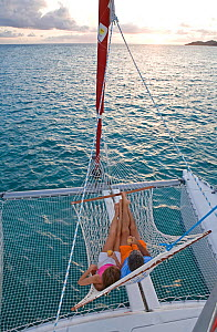 Couple relaxing in hammock onboard Sunsail Lagoon 410 in the British Virgin Islands, April 2006. Model and property released.  -  Billy Black