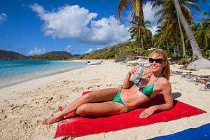 Woman drinking water and sunbathing on a beach in the British Virgin Islands, March 2006. Model and property released.  -  Billy Black