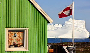 House in Qeqertarsuaq with the national flag flying, iceberg in distance, Qeqertarsuaq, Greenland, August 2009  -  Wild Wonders of Europe / Jensen