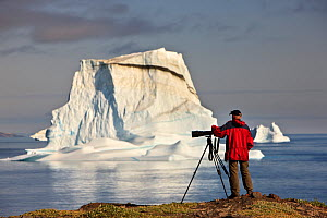 Photographer, Kai Jensen, on the coast near an iceberg, Qeqertarsuaq, Disko Bay, Greenland, August 2009  -  Wild Wonders of Europe / Jensen