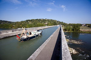 Contessa 26 motoring across the Agen Aqueduct, which carries the canal de Garonne across the Garonne River, France, October 2009. Model Released. - Richard Langdon