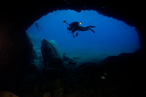 Two divers swimming past cave entrance, Deserta Grande, Desertas Islands, Madeira, Portugal, August 2009  -  Wild Wonders of Europe / Sá