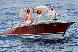 Classically dressed people with sunshades on Riva motorboat. Monaco Classic Week, September 2009.  -  Benoit Stichelbaut