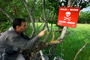 Person pointing at mine warning sign in a mine field near the village of Zadrzani, Northern Livanjsko Polje, an area affected by war (1991-1995) Bosnia and Herzegovina, May 2009 - Wild Wonders of Europe / della Ferrera