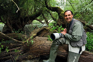 Photographer, Elio della Ferrera, holding camera sitting on fallen tree, in an oxbow of the Sava river flooded area, Lonjsko Polje Nature Park, on the Croatia Bosnia and Herzegovina border, June 2009  -  Wild Wonders of Europe / della Ferrera