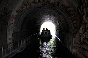 Boat passing through a tunnel on the Canal Du Midi near Capestang, Languedoc, France. July 2009. Model and property released.  -  Billy Black