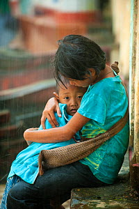 Two children, one sheltering the other, in heavy rain, during the monsoon, Bago, Myanmar, before Burma.  August 2009  -  Inaki Relanzon