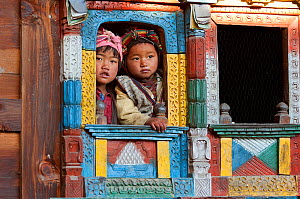 Two children looking through decorated window of traditional building. Tamang ethnic group, Tamang heritage trail, Gadlang, Langtang region, Nepal. November 2009  -  Bernard Castelein