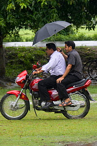 Two men on a motorcycle using an umbrella to protect them from the monsooon rain, Bangladesh, November 2008 - David Woodfall