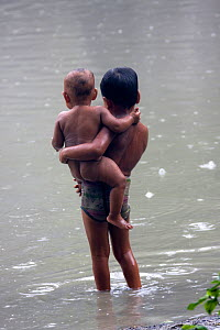 Young Bangladeshi with young brother in monsoon rain washing in pond, Ganges delta, Bangladesh, November 2008  -  David Woodfall
