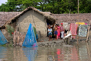 Family with their home threatened by rising sea level, Ganges delta, Bangladesh, July 2008 - David Woodfall