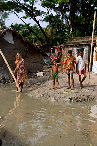 Villagers outside home threatened by rising sea level, Ganges delta, Bangladesh, November 2008 - David Woodfall