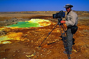 Cameraman, Martyn Colbeck, filming the Dallol hot springs where water heated by magma laden with potassium, sulphur and iron spews up through salt pans staining the salt deposits with vivid colours, i...  -  Chadden Hunter