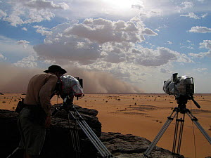 Cameraman, Justin Maguire, makes final adjustments to two timelapse cameras protected by thick plastic covers as a sandstorm approaches at 80km/hour, for the Deserts Episode of the BBC tv series Plane... - Chadden Hunter