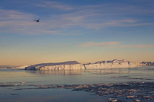 Russian Mi-2 helicopter flies over icebergs on ice reconnaisance in Erebus & Terror Gulf. Weddell Sea, Antarctica, October 2006.  -  Bryan and Cherry Alexander